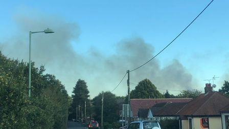 Smoke can be seen over the houses on Dobbs Lane near the heathland. Picture: ARCHANT