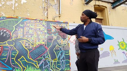 Artist EVEWRIGHT explaining the thinking behind the Stop Loan Sharks mural. PICTURE: RACHEL EDGE