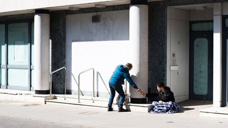 A passer by shares his food with a homeless man. Picture: SARAH LUCY BROWN