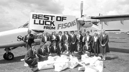 The Ipswich Ladies Hockey Club at Ipswich Airport in 1986. Holding the banner pole is Brian Perks (M
