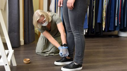 Masks, gloves and protective glasses are worn whilst making alterations to clothing Picture: CHARLO