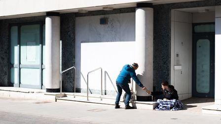 A passer by shares his food with a homeless man Picture:SARAH LUCY BROWN