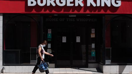 A woman in a mask walks past a Burger King store during lockdown Picture: SARAH LUCY BROWN