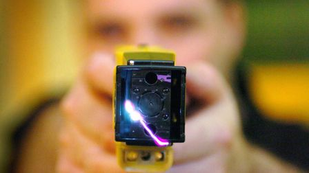 A police officer demonstrating a Taser gun Picture: DANNY LAWSON/PA WIRE