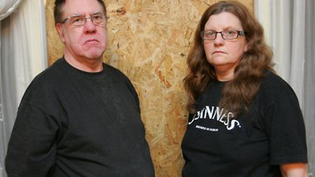 Kenny and Kathleen Rogers with their boarded-up window