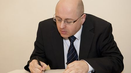 Leader of the council Cllr Keith Prince signing the armed forces agreement