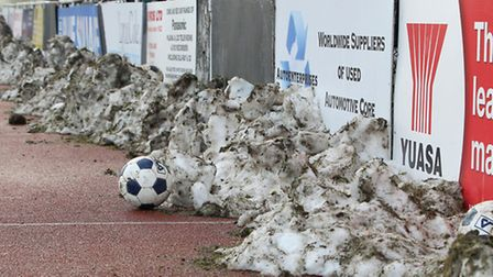 Snow lies around the pitch at Bridge Avenue, having been cleared by fans to ensure Hornchurch's game