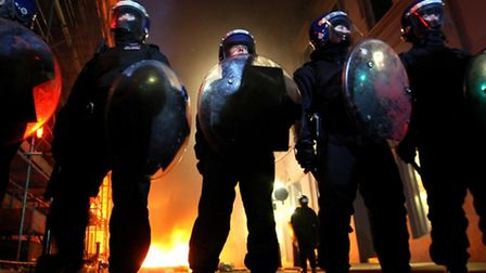 Police from the Territorial Support Group are seen in front of burning dustbins during the 'March fo