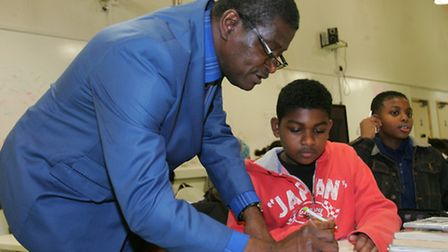 Pastor Gbola Bright helps Jonathan Dookie with his sums