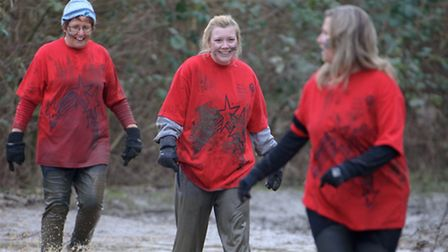 Women from The Athena Network wade through the mud as part of the challenge