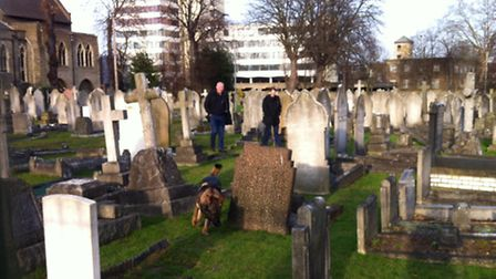 A police dog team sweep the churchyard for anything thrown by the suspect.
