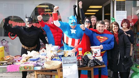 Superheroes from Tate and Lyle Sugars in East London invade Richard House charity shop in Dagenham H