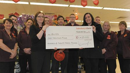 Sainsbury's HR manager Kiera Murphy presents a cheque for £1,423 to Sam Marsland, champion for Bliss