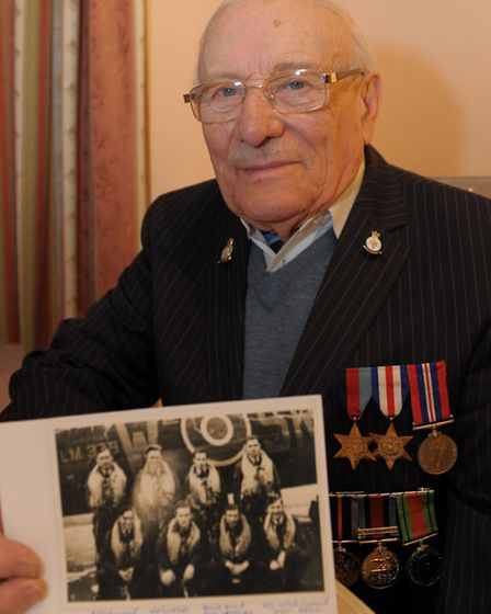Leslie Templ holds a photo of his crew men at their squadron base in Ludford Magna, ( he is front ro