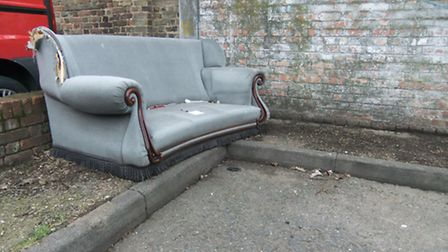 An abandoned couch in a Romford town centre business car park