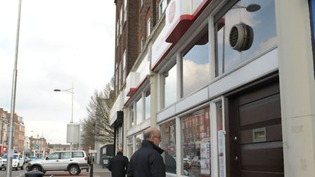 A customer reads the sign put on the door to explain the closure of Barkingside Post Office.