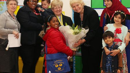 Kira Noronha, seven, presents flowers to Headteacher Nina Panayis as she retires after five years of