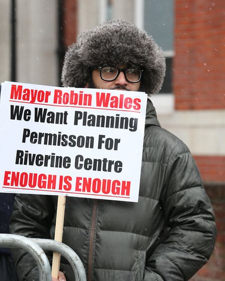A Newham People's Alliance supporter braves freezing temperatures as they protest outside East Ham T