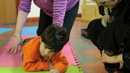 Pauline helps Abdullah, two, do some basic exercises, watched by mum Amna Rehan