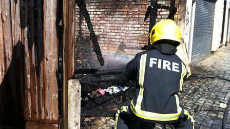 A firefighter dampening down the wreckage after the fire in Hobbs Mews, Seven Kings.