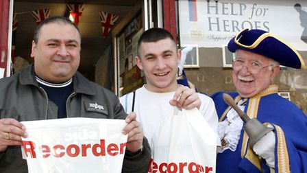 Chris Haigue (L) and Anron Hajaig (second L) of Aaron's Surplus Army and Navy with town crier Harry