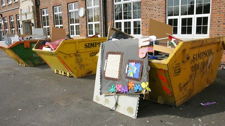 Skips filled with ruined books, toys and children's work.