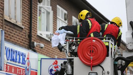 The woman, whose feet are visible, was removed from the flat and taken to hospital (photo: Ellie Hos