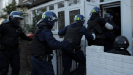 Police rush into a house in Stratford. Picture: David Mirzoeff