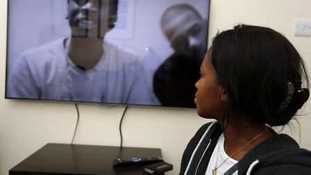 Champion's mother Peguy Kato watching one of his videos on YouTube (photo: Ellie Hoskins)