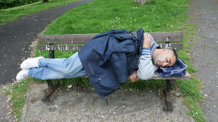 A homeless man sleeping rough on a bench in Ilford