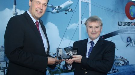 Declan Collier, CEO of London City Airport, right, receives the award from Frank Brenner, Director G