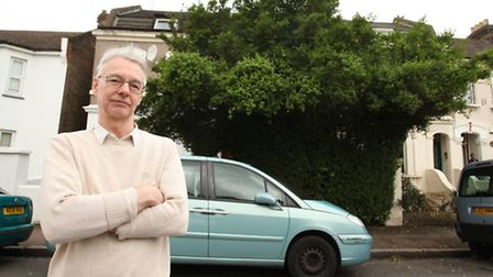 Dr Michael Pelling stands in front of his house's high hedge, which is upsetting his neighbour (righ