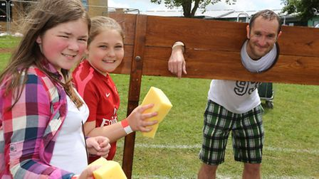 Amy Mason, 11, and Leah Webb, 11, with headteacher Malcolm Drakes in the stocks.