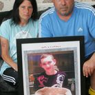 Luke's mum Caroline and stepdad Anthony Dray with a picture of Luke