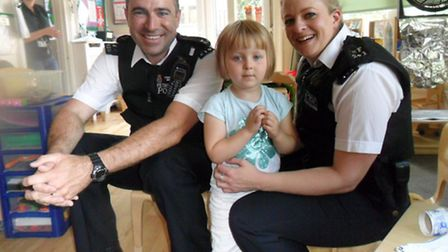 Matilde Kvist-Waddell, aged three, with Newham police officers during their visit to Chestnut Nurser