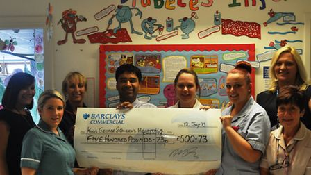Pharmacist Dinesh Gupta and his colleagues with the money he raised for the King George and Queen's
