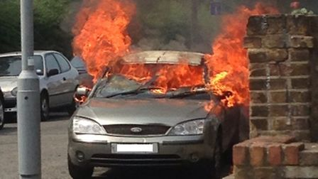 The Ford Mondeo on fire in Brisbane Road shortly after the robbery