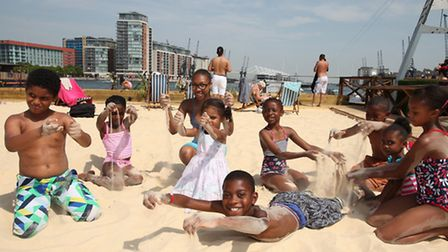 Children play in the sand at the Royal Victoria Beach at Royal Victoria Docks