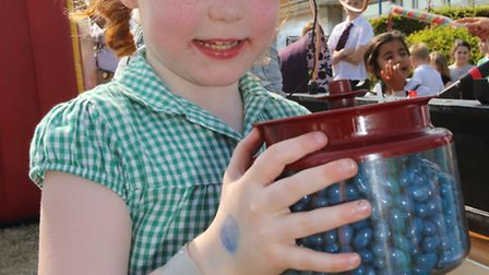 Mia Wheatley, four, tries to guess how many blueberries are in the jar.