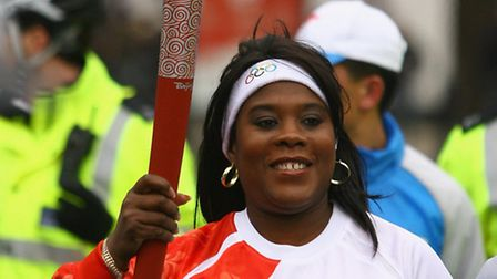 British former Olympic javelin thrower Tessa Sanderson carries the Olympic torch during its relay jo