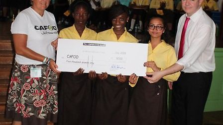 Denise Griffith & Headteacher Mark Johnson & students presenting the cheque for £5000 to CAFOD