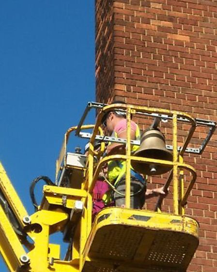 Construction workers on a cherry picker installing the new bell.