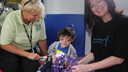 Helen Jackson, a nurse at Haven House with a three-year-old patient, and barclays volunteer Cid Pete
