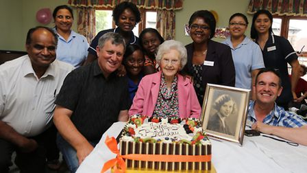Renne Underhil with her cake and her family and staff, with a picture of her when she was younger on