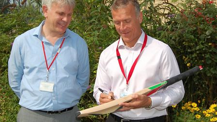 Cricketing legend Alec Stewart signs a bat for Peter Ellis, CEO at the hospice