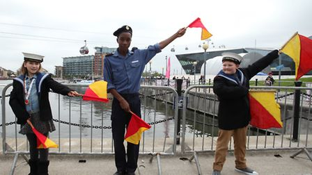 OC Dean Goss, from the Sea Cadets, shows Elena Caswell, left, and Callum Petheis some flags signal a