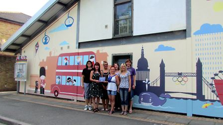The transformed wall with its colourful mural and delighted staff Picture: Picasa