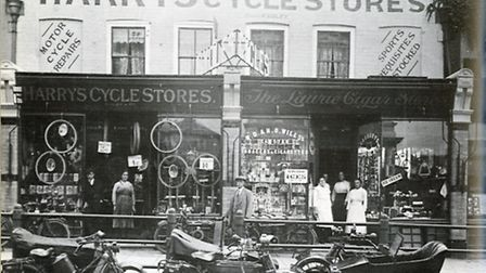 The shops in Market Place in 1917 include Harry's Cycles Stores. Owner Harry Sibley stands between