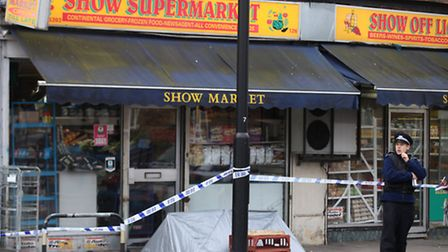 Forensics investigate the shooting of two shop workers at Show Supermarket in High Street, Plaistow,
