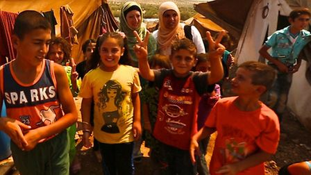 Dr Ahsan (back right) with Dr Hallam (back left) and children at a Syrian refugee camp. Courtesy of